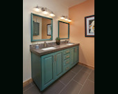 Eclectic Guest Bath, Slate countertop with dual under mounted sinks and iridescent glass tile backsplash.  Refurbished Alder wood vanity in glazed teal.  Custom mirrors and porcelain tile floors.