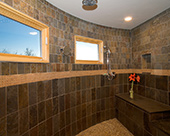 Master Bath with dramatic walk-in rain shower featuring Pella windows with slate wall tiles and bench top and pebble tile floor.  Accented with glass deco tile.