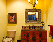 Mexican Rustic powder room with Saltillo tile floors and a custom hand chiseled antique furniture bathroom cabinet base, copper sink, oil-rubbed bronze faucet, iron chandelier and custom hand painted faux finish walls