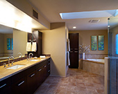Master Bath remodel with ebony stained Bellmont alder cabinets accented with Danze fixtures, walk-in shower, under mounted jetted tub with roman tub assembly, and glass tile bathroom walls accents, double dome skylights illuminated by Tucson AZ sunshine