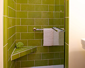 Inviting & invigorating bathroom remodel, shower surround with spring green staggered subway tile,  corner bathroom shower bench and with clear glass shower door