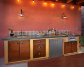 Rustic Mexican Outdoor Kitchen, Green slate countertop with Mexican tile backsplash.  Stainless steel sink with two-burner cooktop, under counter refrigerator, and storage cabinetry in rich rusted patina metal.  Tinted stucco finished wall with cantina lighting.