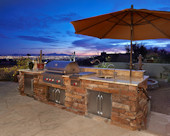Old World Tuscan Outdoor Kitchen, Wolf grilling station with side-burner.  Granite countertop in sandstone on cultured stone base with stainless steel sink, under counter refrigerator, and storage.  Natural flagstone patio.