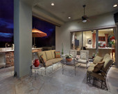 Contemporary Tuscan Outdoor Living Room, Painted stucco in taupe-grey, electronic western facing sunshade, recessed lightening and sound system.  Wrought iron furnishings and natural flagstone flooring.