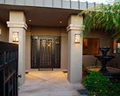 Front Entry/Courtyard with fountain, custom designed iron security door and gate, standing seam metal roof and stucco columns