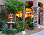 Front Entry with stack stone columns custom iron front entry door, Cantera fountain.