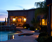Back yard custom pool and spa, elevated banco wrapped with stack stone, concrete CDI fire pots, bronzed finials, Granite tile pool splash, Pentair Magic Stream pool lighting LED luminars, and flagstone walkways
