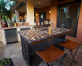 Outdoor Kitchen with travertine floors, metal island cabinets on wheels with glass tile countertops granite counters at perimeter, Elkay sink and under cabinet refrigerator