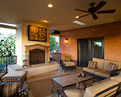 Outdoor Living Room with stucco face fireplace and travertine hearth, metal and glass enclosure for flat screen TV