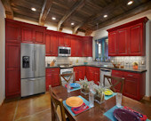 Old World Spanish, Refurbished cabinetry lacquered in red with black glaze.  Reclaimed wood beam ceiling, stained and sealed.  Moroccan inspired patterned backsplash with black slate countertops.  High-polished stained concrete floors.