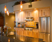 Southwest Traditional, Natural Hickory wood cabinets.  Marble backsplash in sunflower with pewter decorative inserts and border.  Hand-blown glass LED pendants suspended over granite countertops with bi-level breakfast bar.